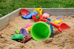 Children's sandbox with toys. Wooden children's sandbox with the scattered toys Royalty Free Stock Photo