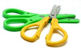 Children's scissors. Two pairs of kids' scissors, green and yellow Royalty Free Stock Photography