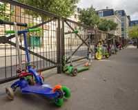 Children's scooters are locked to school yard fence in Paris Royalty Free Stock Image