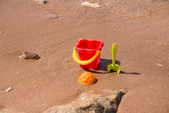 Children`s set for game with sand on the seashore. Plastic Beach toys near water. Kids fun on vacation near sea. Games Stock Image