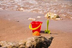 Children`s set for game with sand on the seashore. Plastic Beach toys near water. Kids fun on vacation near sea. Games Royalty Free Stock Photo