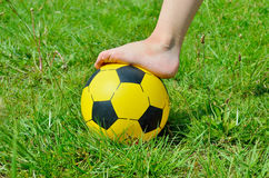 Children's shoeless foot and a soccer ball on green grass Royalty Free Stock Photography