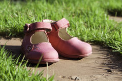 Children's shoes. Pink children's shoes on a stone plate in a green grass Royalty Free Stock Image