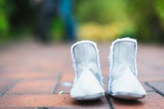 Children`s shoes on the background of a man and a pregnant woman. Horizontal frame Royalty Free Stock Photo