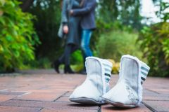 Children`s shoes on the background of a man and a pregnant woman. Horizontal frame Stock Images