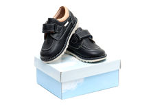 Children's shoes on the box. Black children's new shoes are on the box on a white background Royalty Free Stock Photos