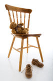 Children's shoes, chair and teddy bear royalty free stock image