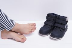 Children`s shoes and feet. On white background Royalty Free Stock Image