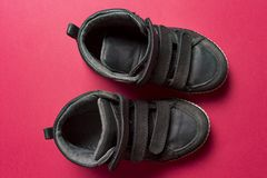 Children`s shoes made of black leather on a pink background. stock photography