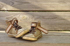 Children's shoes. Old children's shoes on the background of the wooden planks Royalty Free Stock Photos