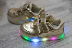 Children`s shoes on a wooden surface stock image