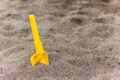 Children`s shovel in the sand on the beach stock photos