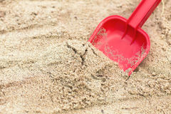 Children's shovel in the sandbox. Baby red shovel stuck in the sandbox on the playground Royalty Free Stock Photo