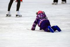 Children s skate rink. A little boy skates and falls on the ice in winter Active family sport during the winter holidays. And the cold season. School sports stock images