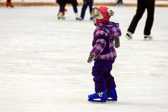 Children s skate rink. A little boy skates in the winter. Active family sport , the winter holidays and the cold season.School. Sports clubs royalty free stock photo