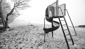 Children's slide at the beach. Black and white of a children's spiral playground slide on a cold November morning - empty beach in Ontario Canada Royalty Free Stock Image
