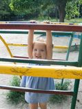 Children's small town. The girl on a children's playground plays on gymnastic ladders Royalty Free Stock Photo