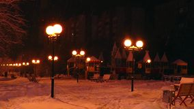 Children's snow-covered town, lit by street lights in the polar night. stock video footage