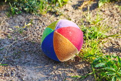 Children's soft fabric and striped multi-colored ball about the gray stones round the foot of the alpine hills in the green grass. Royalty Free Stock Photo