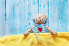 Children's soft toy teddy bear in bed with thermometer and pills, take the temperature of a mercury glass . On  blue Royalty Free Stock Photography