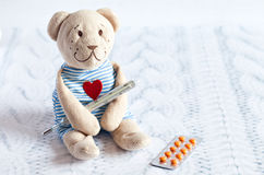 Children's soft toy teddy bear with pills takes the temperature of a mercury glass thermometer. child' disease. Royalty Free Stock Photos