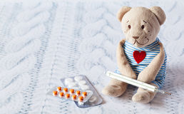Children's soft toy teddy bear with pills takes the temperature of a mercury glass thermometer. child' disease. Stock Photo