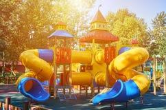 children' s speelplaats in een openbaar park, kid' s vermaak en recreatie, zonlichteffect stock afbeelding