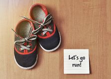 Children`s, sports sneakers. And sticker reminder on a wood background royalty free stock images