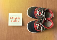 Children`s, sports sneakers. And sticker reminder on a wood background stock photo
