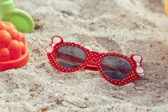 Children's sunglasses  lie on a beach on sand Royalty Free Stock Photos
