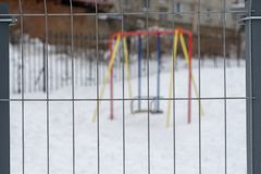 Children`s swing behind the fence. focus on the fence