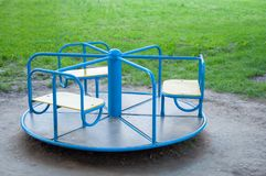 Children`s swing carousel blue. At the playground. On the background of green grass. stock photography