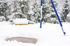 Children's swing in the snow Stock Image