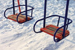 Children's swings against the winter snow. Close-up Royalty Free Stock Photography