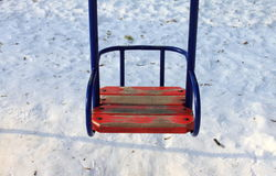 Children's swings against the winter snow. Close-up Stock Photo