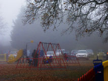The children`s swings foggy morning in Harrow park. Stock Photos