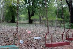 Children`s swings hang empty an idle at a playground on a dull, overcast day. Lost child day.  royalty free stock photos