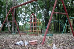 Children`s swings hang empty an idle at a playground on a dull, overcast day. Lost child day.  stock image