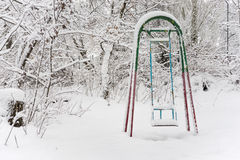 Children's swings in winter park Stock Photography