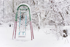 Children's swings in winter park Royalty Free Stock Photos