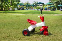 Children`s three-wheeled red and white bicycle on green grass royalty free stock photo