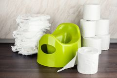 Children`s toilet pot green, nappies and toilet paper, the concept of the baby`s transition from diapers to the toilet. Children`s toilet pot green, nappies and royalty free stock photos