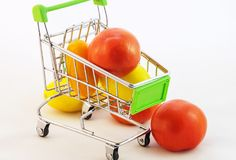 Children`s toy cart for purchases which are tomatoes Royalty Free Stock Photo