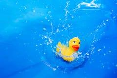 Children's toy duck drop into water Stock Photo