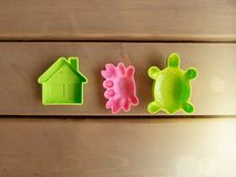 Children`s toy green house, pink crab and green turtle on the wooden floor of a country house. Sun glare. Horizontal orientation, stock photography