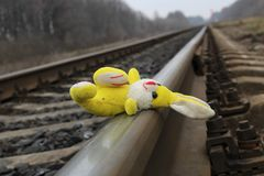 Children`s toy lies on the train rails. Stock Photos
