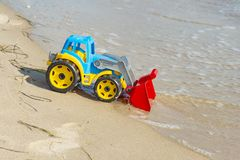 Children`s toy tractor on the sand at sea stock photos