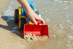 Children`s toy tractor on the sand at sea royalty free stock photo