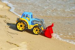Children`s toy tractor on the sand at sea royalty free stock images