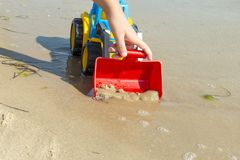 Children`s toy tractor on the sand at sea stock image